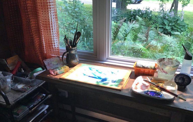 Matériel d'art devant une fenêtre donnant sur de la verdure.